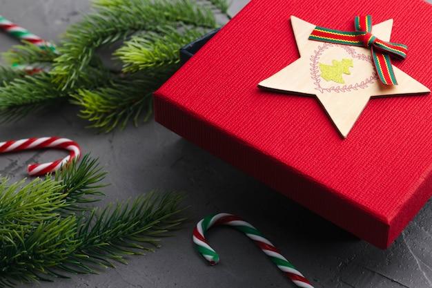 Ramas de abeto sobre fondo gris concreto con caja de regalo roja y decoraciones
