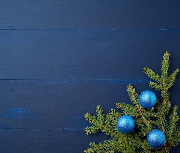 Ramas de abeto verde y bolas de navidad brillantes de color azul oscuro