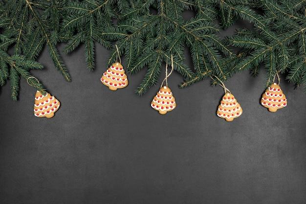 Ramas de abeto verde como un árbol de navidad en forma de marco y galletas sobre un fondo de pizarra negra. maqueta abstracta con espacio de copia