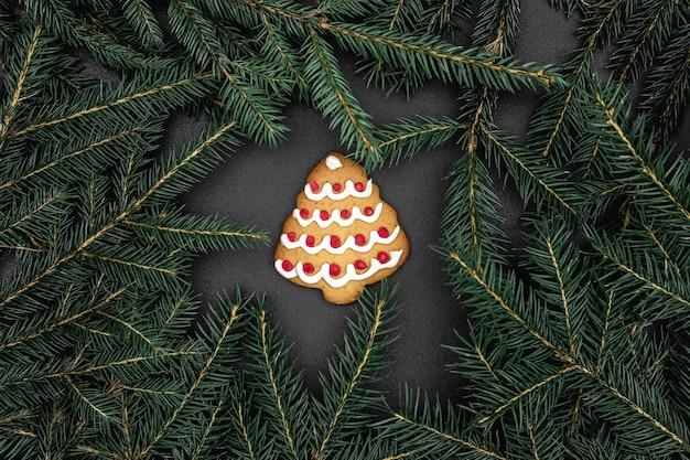 Ramas de abeto verde como marco y árbol de navidad en forma de galleta sobre un fondo de pizarra negra. maqueta abstracta con espacio de copia