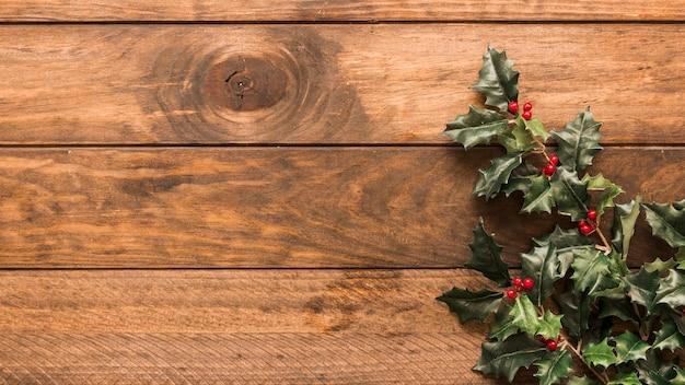 Ramas de acebo en mesa de madera