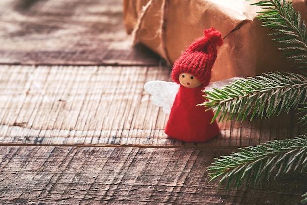 Ramas de árbol de abeto de ángel de navidad divertido y cajas de regalo sobre fondo nevado de invierno con ramas nevadas. concepto de navidad o invierno.