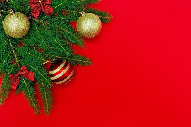 Las ramas del árbol de navidad con bolas de oro y un lazo en rojo.
