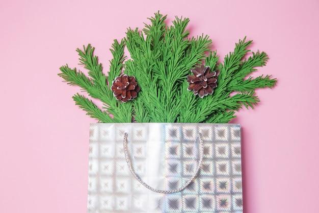 Ramas de árbol de navidad verde con conos en una bolsa de regalo