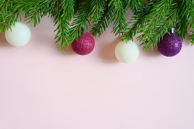 Ramas de los árboles de navidad con adornos navideños juguetes bolas, marco sobre un fondo rosa. espacio para texto