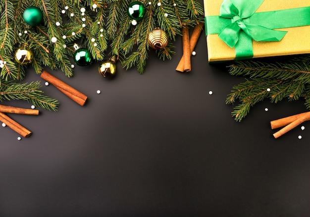 Las ramas de los árboles de navidad decoraron juguetes y palitos de canela con caja de regalo sobre un fondo negro, lugar para el texto. fondo de navidad.