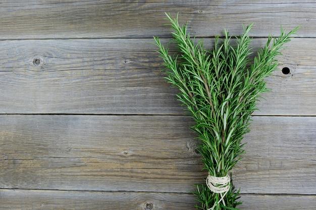 Ramas de bio romero orgánico fresco, atado en un montón por una cuerda en una vieja mesa de madera.