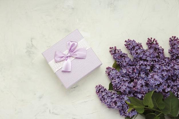 Ramas de color lila, caja de regalo sobre una superficie de piedra clara. concepto de primavera. vista plana, vista superior