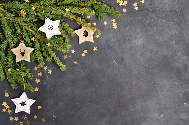 Las ramas, decoración de estrella de madera, confeti dorado sobre oscuro