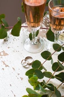 Ramas de eucalipto con copas de vino rosado y anillos de boda