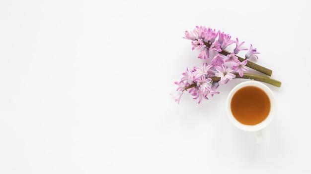 Ramas de flor morada con taza de té