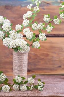 Ramas florecientes en un florero en una textura de madera.