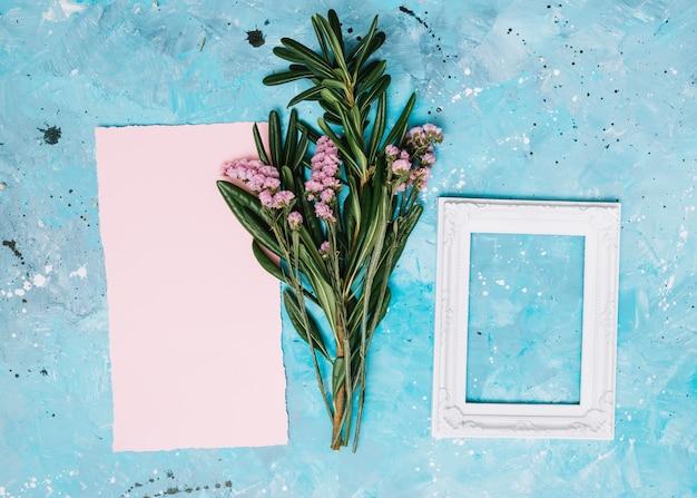 Ramas de flores con marco en blanco blanco en mesa azul