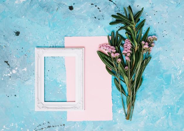 Ramas de flores con marco en blanco en la mesa azul