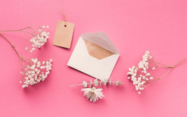 Ramas de flores con sobre en mesa rosa