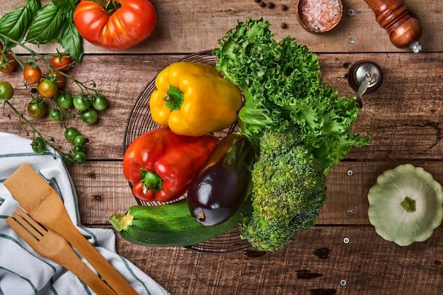 Ramas frescas de tomate cherry, hojas de albahaca, servilleta, pimiento y molinillo de pimienta sobre fondo rústico de madera vieja. fondo de cocción de alimentos y maquetas.