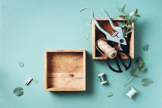 Ramas y hojas de eucalipto, podadora de jardín, tijeras, cajas de madera.