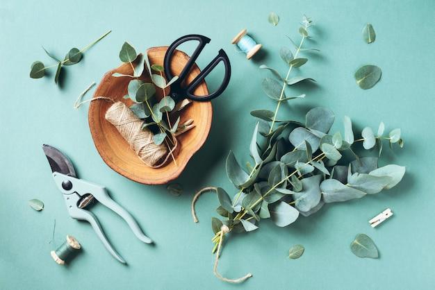 Ramas y hojas de eucalipto, podadora de jardín, tijeras, placa de madera