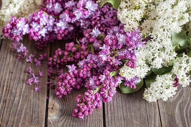 Ramas de lilas frescas en flor sobre una mesa de madera oscura.