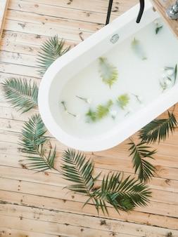 Ramas de palmera con flores vista superior en una bañera y sobre fondo de madera