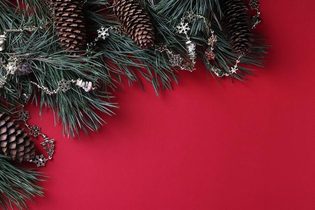 Ramas de pino con conos y guirnaldas en superficie roja. espacio para deseos. vista superior. espacio para deseos