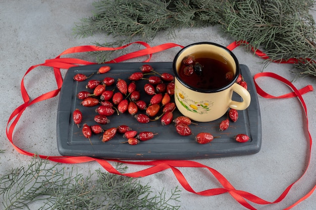 Ramas de pino natural junto a la bandeja azul marino de escaramujos y una taza de té de rosas para perros rodeada de cintas en la superficie de mármol