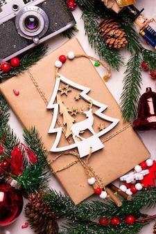 Ramas de pino y regalos de navidad en una mesa blanca