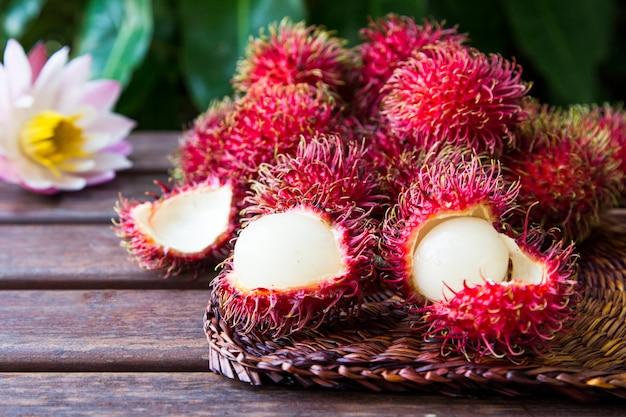 Rambutanes maduros frescos en fondo de madera. deliciosa fruta dulce de rambután.