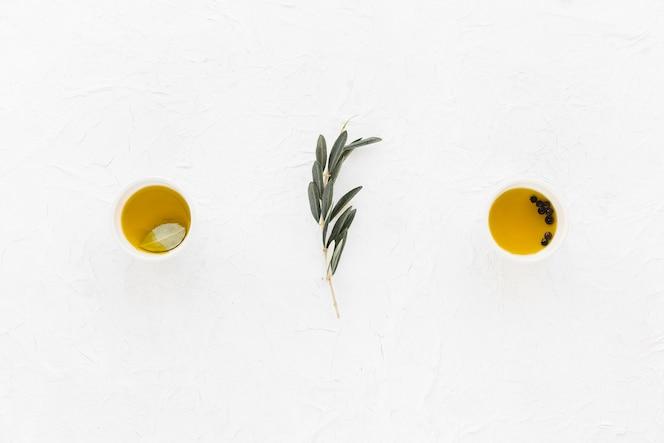 Ramita de olivo con pimienta negra y aceite de oliva en los tazones