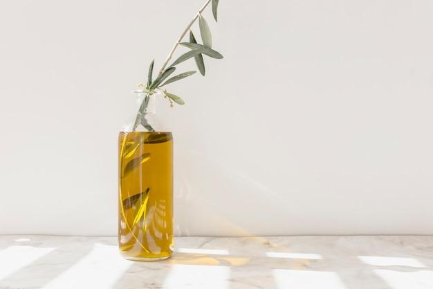 Ramita dentro de la botella de vidrio de aceite abierta en el piso de mármol