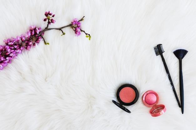 Ramita de flor morada con polvos faciales compactos y pinceles de maquillaje sobre fondo de piel