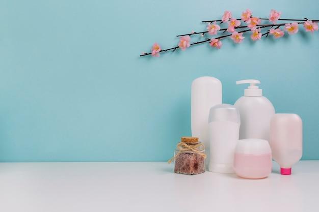 Ramita floreciente sobre botellas de cosméticos y tarro