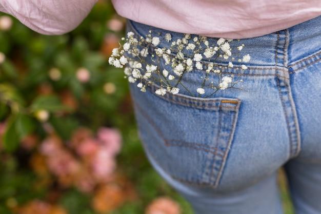 Ramita con flores blancas colocada en el bolsillo trasero de jeans de mujer.