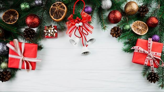 Ramita navideña con campanas y cajas presentes.
