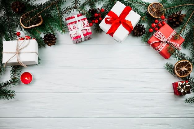 Ramita navideña con velas y cajas presentes.