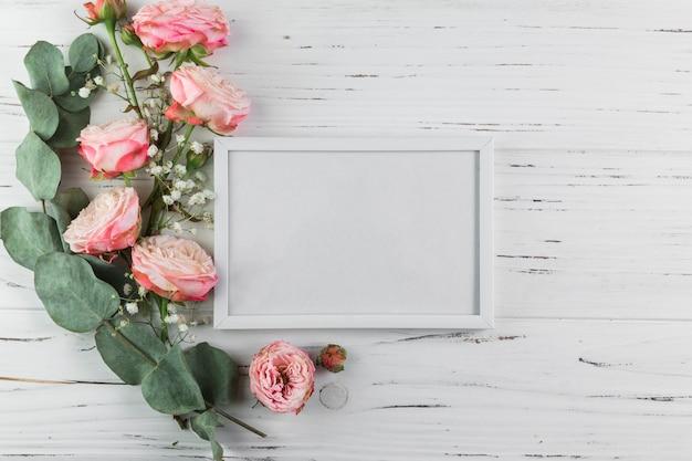 Ramita; rosas y flores de aliento del bebé cerca del marco blanco en blanco sobre superficie con textura de madera