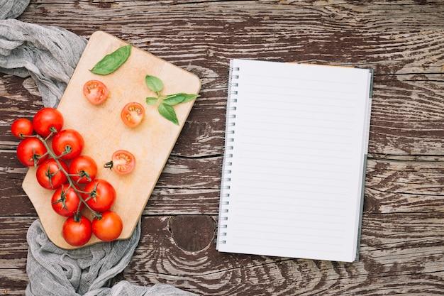 Ramita de tomates cherry y albahaca sobre tabla de cortar y cuaderno de notas en espiral sobre el escritorio de madera