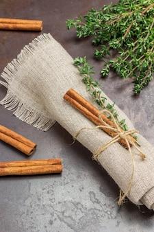 Ramita de tomillo y canela en rama sobre una servilleta de lino. ramitas de tomillo y ramitas de canela en la mesa.