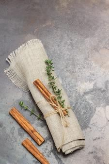 Ramita de tomillo y canela en rama sobre una servilleta de lino.