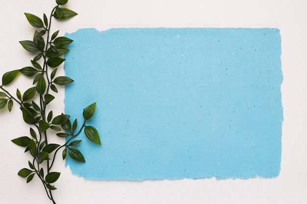 Una ramita verde artificial cerca del papel rasgado azul sobre fondo blanco.