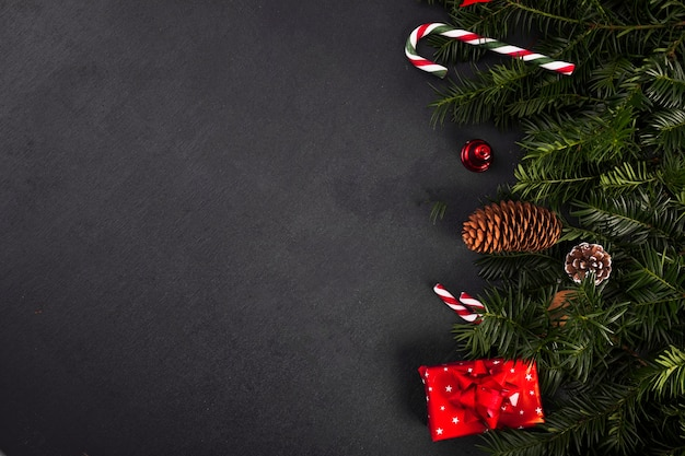 Ramitas de abeto cerca de bastones de caramelo y caja de regalo