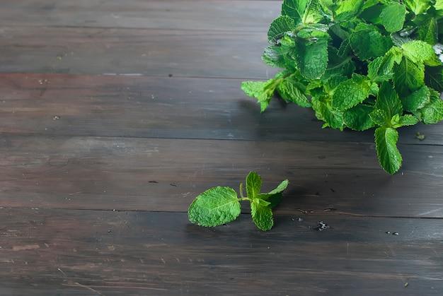 Ramitas de menta frescas y orgánicas en la mesa de madera.