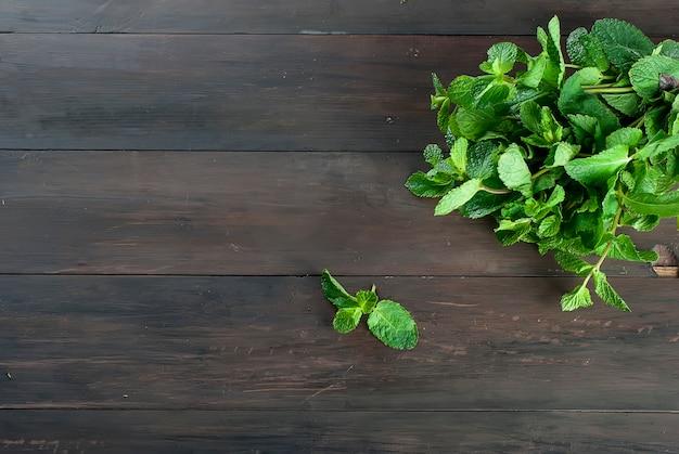 Ramitas orgánicas frescas de menta en la mesa de madera