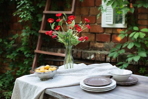 Ramo de amapolas en jarrón terraza interior patio mesa y platos para el almuerzo en el jardín en el patio