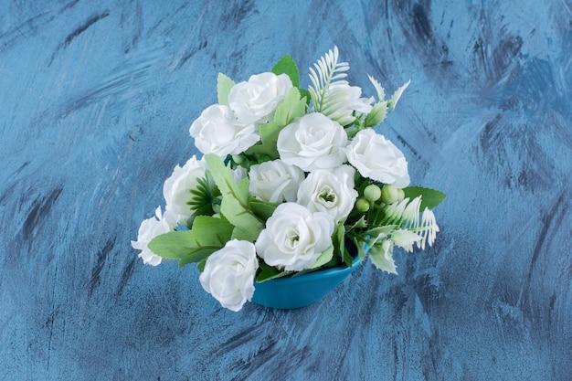 Ramo con arreglo de rosas blancas naturales sobre azul.