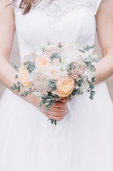 Ramo de boda de belleza de flores rosas y ramas de eucalipto en manos de la novia.