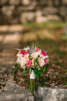 Ramo de boda de rosas peonías y suculentas en las rocas