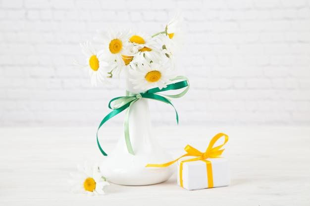 Ramo de chamomiles en un jarrón blanco sobre un fondo de ladrillo blanco