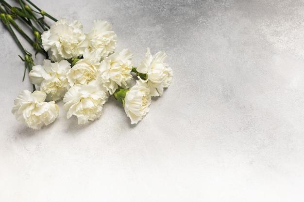 Ramo de claveles blancos sobre un fondo gris