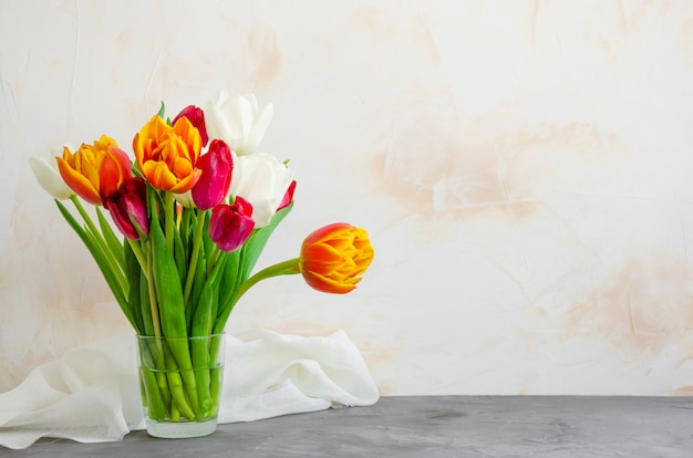 Ramo de coloridos tulipanes naturales en un florero de vidrio con agua sobre un fondo de hormigón.